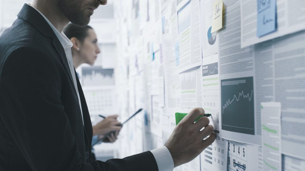 Business people checking financial reports on a wall